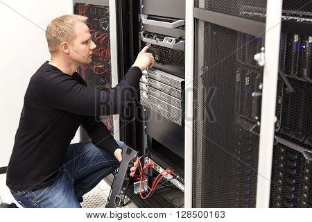 It engineer or consultant work with server in data rack. Shot in large datacenter. poster