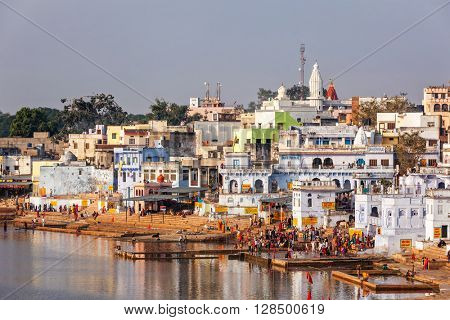 PUSHKAR, INDIA - NOVEMBER 20, 2012: Hindu devotees pilgrims bath in sacred Puskhar lake (Sagar) on ghats of  Pushkar, Rajasthan, India. Pushkar is holy city for Hinduists famous for many Hindu temples