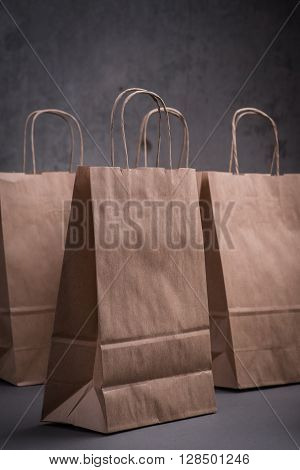 Four Craft Paper Bags Over The Greyl Background