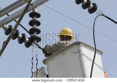 Close-up view of one electrician is repairing electric power system on hydraulic platform.