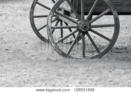 closeup of monochrome tone fragment of the ancient wooden animal-drawn vehicle with spoke wheels