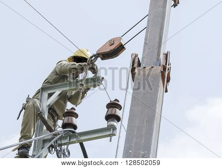 One electrician climbing on electric is repairing electrical power system for normal working. Closed-up view.