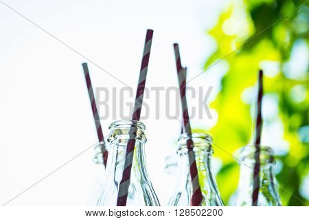 Glass Bottles With Straws Over The Sunny Background
