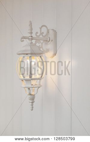 the metal white forged candelabrum on a white wooden wall