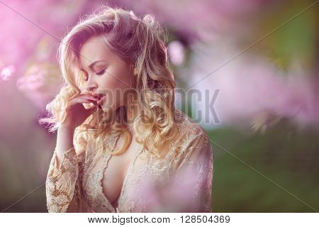 Sensual young woman standing in sexy transparent dress at blossoming pink sakura tree in the garden. Beauty of woman and nature.Portrait of beautiful model with curly blonde hair. Closed eyes in passion