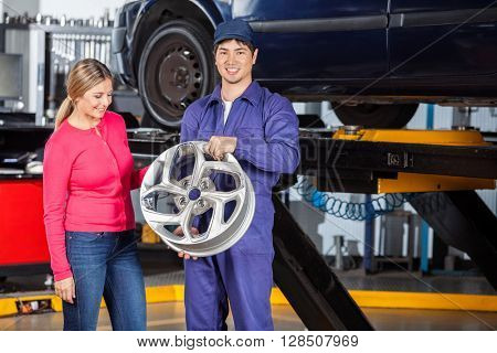Mechanic Holding Hubcap With Customer Examining It
