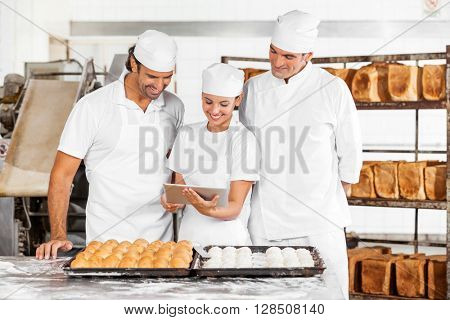 Baker's Using Tablet Computer While Preparing Breads In Bakery