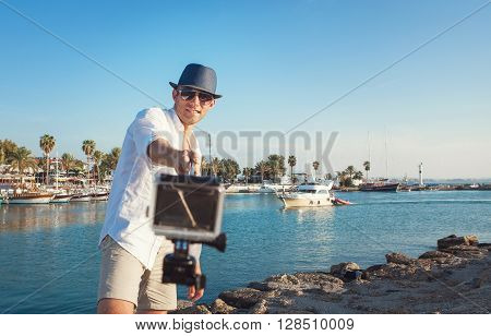 Man with action camera take a selfie photo in the tropical sea bay