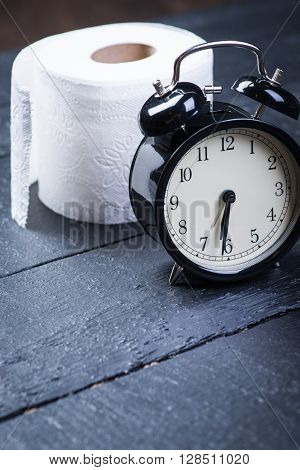 Alarm clock with toilet paper on a black wooden table