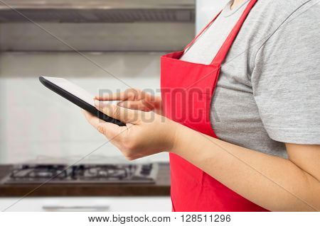 woman looking online a recipe on her digital tablet while preparing a meal at the kitchen
