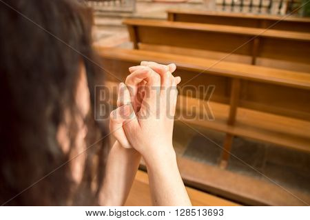 detail of woman praying in a pew at a church with joined hands