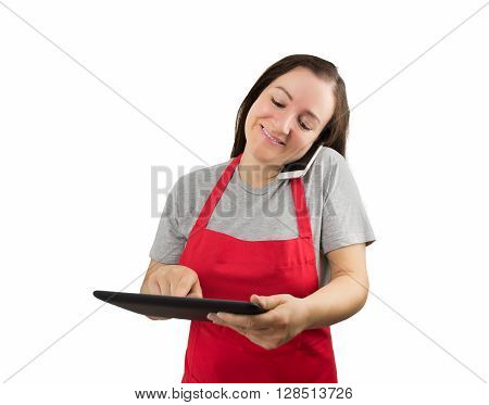 saleswoman with apron talks by smartphone and uses a tablet at the same time poster