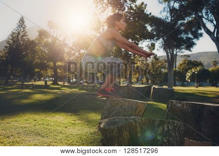Shot of a young woman jumping onto wooden log at the park. Sportswoman doing exercise in nature on a sunny day. Box jumps.