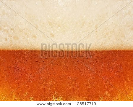 Beer with foam in glass taken closeup suitable as abstract background.