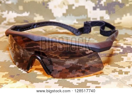 The Military tactical goggles on camouflage background.