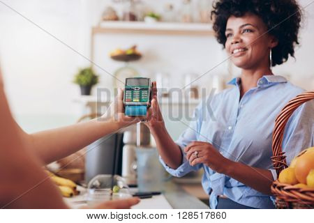 Female Customer Paying For Her Juice By Credit Card