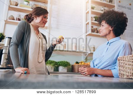 Two Young Female Employees Standing Behind Juice Bar Counter
