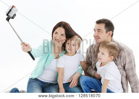 Happy family making selfie with selfie stick isolated on white
