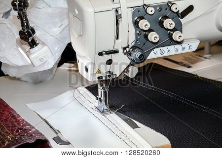 Single-needle lockstitch sewing machine with bag platform with triple unison promotion for medium and heavy materials