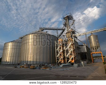 Grain silos and the dryer machine with spare parts for new dryer on the foreground