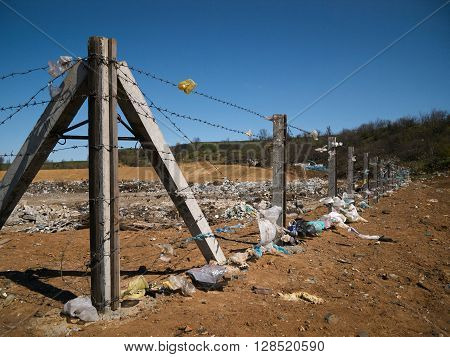 Poles connected with barbwire barrier big garbage dump