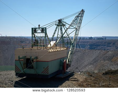Dragline works at small open cast iron mine filled by water with industrial buildings in the background