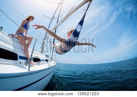 Two women relax on the sail boat moving in the sea