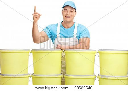 Male decorator pointing up with his finger and standing behind a bunch of buckets isolated on white background