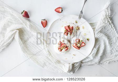 Small strawberry and pistachio pavlova meringue cakes with mascarpone cream, fresh mint over white backdrop, top view