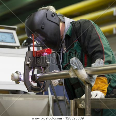 Industrial operator setting  computer controlled process of orbital welding machine in inox pipes manufacturing workshop. Square composition.