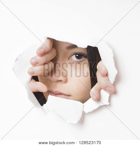 young asian woman tearing hole in paper wall to peek through