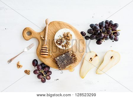 Camembert cheese with grape, walnuts, pear and honey on oak serving board over white rustic wood backdrop, top view copy space