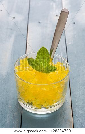 Fresh Lemon slushie in glass on blue wood