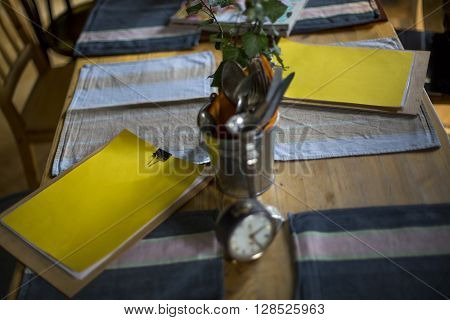 Yellow clipboards on a nice concept table with vintage cutlery