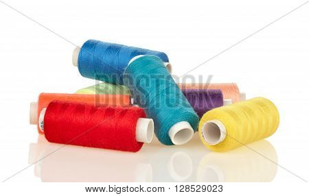 Heap spools with multicolored threads isolated on white background