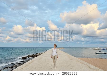 woman walking on the quay - conceptual image freedom serenity peace of mind positive harmony