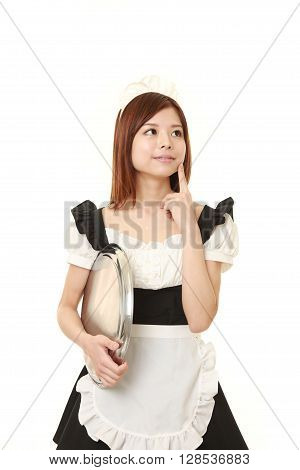 young Japanese woman wearing french maid costume thinks about something