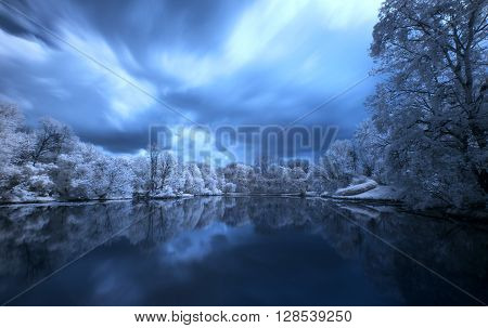 Trees on the lake with a reflection in the water, Polish landscape. Photo Infrared