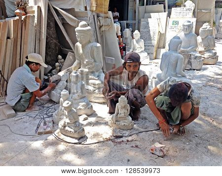 Mandalay, Myanmar - April 20 : Burmese man are carving traditional marble Buddha statues sitting in a street of Mandalay Myanmar (Burma) on April 20 2013 in Mandalay Myanmar