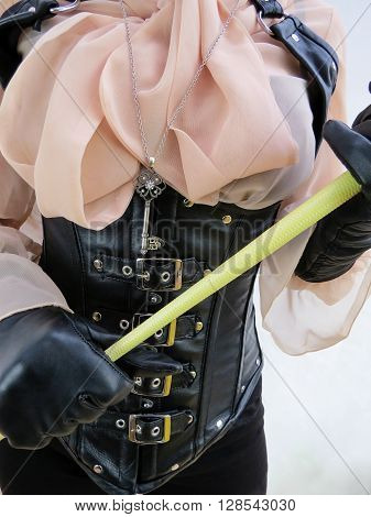 Dominatrix in black corset gloves and bow blouse with chastity key and whip.