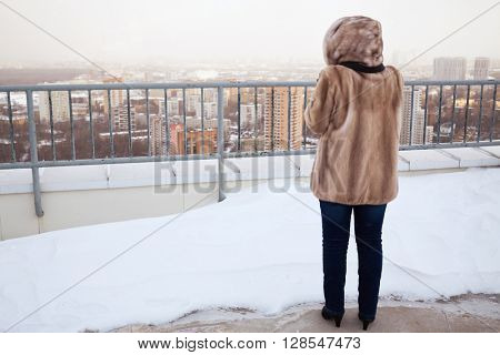 Woman in fur jacket stands on building roof with snowbank in winter, rear view.