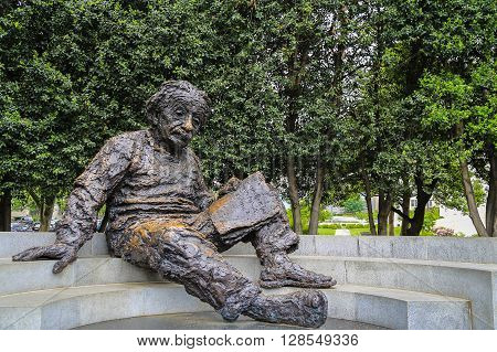Washington DC USA - May 16 2014: Iron statue of Albert Einstein reading a book sits on a flat stairs with trees as a background