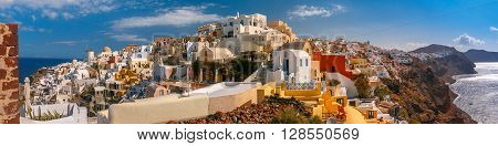 Picturesque panorama, Old Town of Oia or Ia on the island Santorini, white houses, windmilles and church with blue domes, Greece