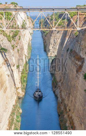 Ocean yacht passes through the narrow Corinth canal. Greece.