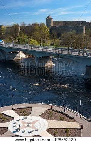 Ivangorod-Narva, Estonia-Russia - May 4, 2016: ancient fortress at the border of Russia and Estonia. The Two Towers shares the Narva River. In the foreground promenade.