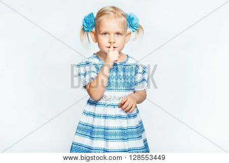 Little beautiful blond girl on a white background making shh