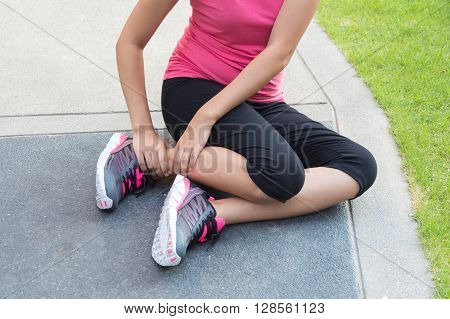 Sporty woman get hurt with twisted ankle.