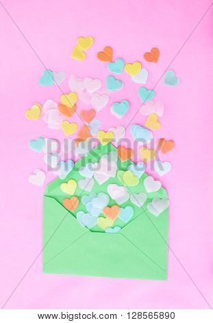 Heart confetti in a green envelope on pink