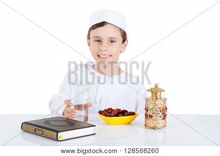 Young Muslim boy ready for brakfast in Ramadan - sitting on a table with water dates Quran and Ramadan lantern