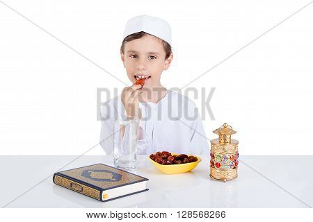 Young Muslim boy eating dates for brakfast in Ramadan - sitting on a table with water dates Quran and Ramadan lantern
